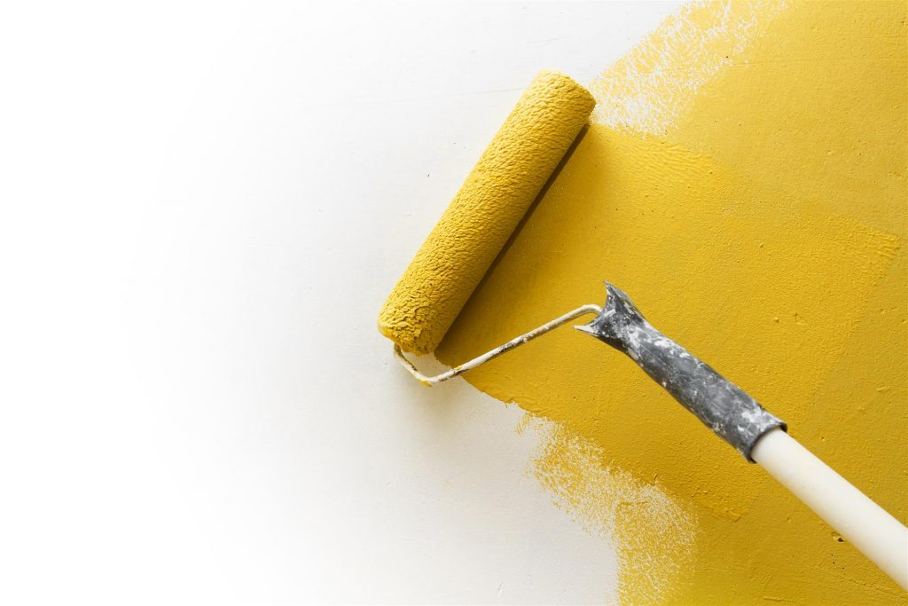Paint Roller Applying Yellow Paint on Wall